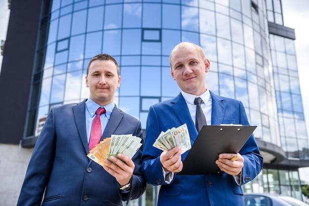 Due uomini d'affari che mostrano le banconote del dollaro e dell'euro