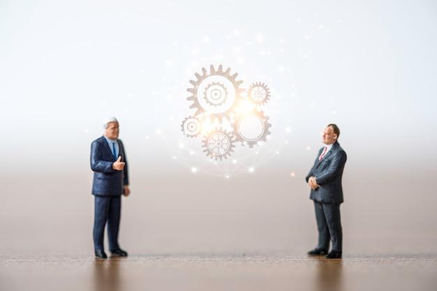 Due uomini d'affari in piedi e discussione con ingranaggi a cremagliera. concetto di idea di brainstorming.