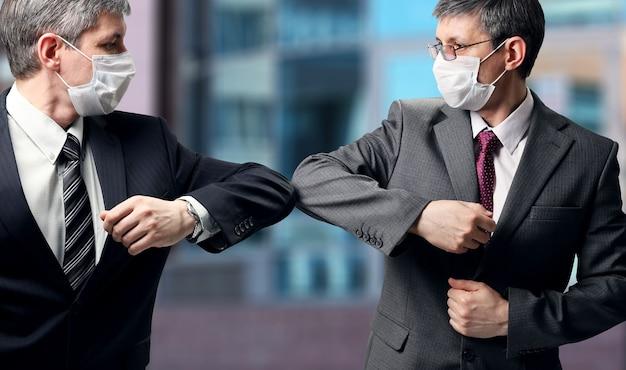Due uomini d'affari con maschera medica salutano in un modo nuovo, colpendo con i gomiti invece della stretta di mano