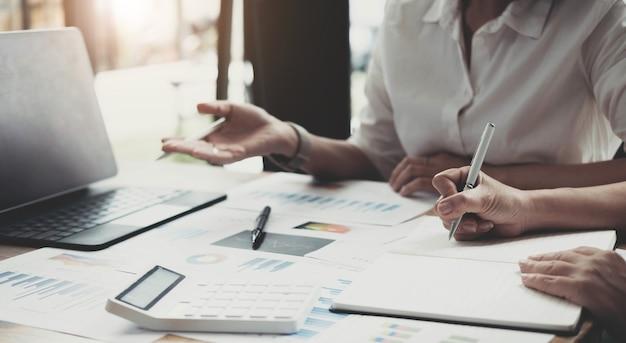 Due imprenditrici stanno lavorando insieme per fare un brainstorming su come far crescere l'azienda e fare piani per controllare le finanze dell'azienda in conformità con il piano. concetto finanziario.