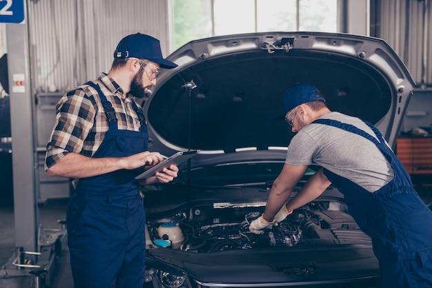 Due esperti ingegneri meccanici impegnati in officina in speciale uniforme blu