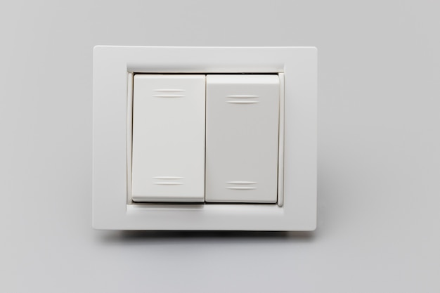 Interruttore bianco a due pulsanti su sfondo grigio. elettricista domestico per la riparazione. concetto di risparmio energetico. avvicinamento. concentrazione completa. copia spazio.