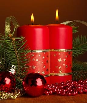 Due candele e decorazioni natalizie, su sfondo marrone