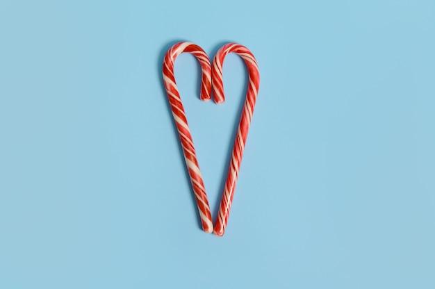 Due bastoncini di zucchero sono disposti su uno sfondo blu a forma di cuore. disposizione piatta di lecca lecca di natale con spazio di copia per l'annuncio