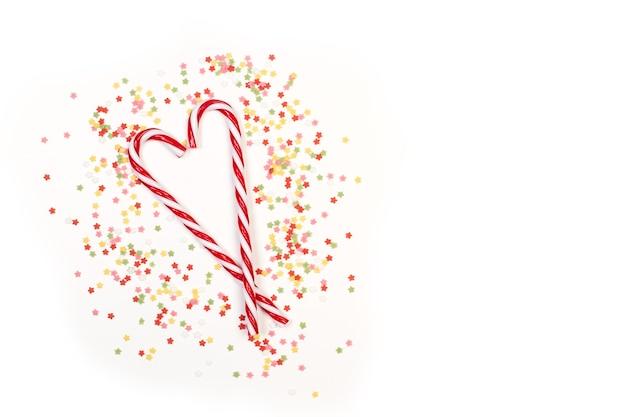 Due bastoncini di zucchero e confetti stella colorati su sfondo bianco