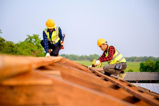 Due falegnami stanno lavorando al cantiere. realizzazione della struttura del tetto in legno. idee per ristrutturare e ampliare case in legno.