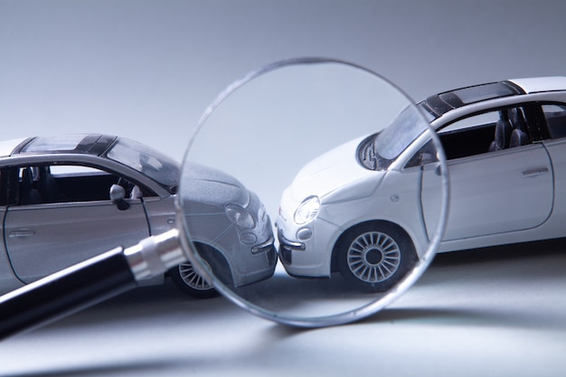 Due auto si sono scontrate, assicurazione. macchine e lente di ingrandimento sul tavolo
