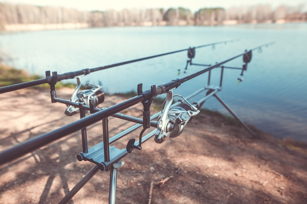 Due canne da pesca colate sulla cremagliera in riva al lago, pronte per la pesca, il carpfishing, la pesca sportiva, il concetto di sport