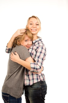 Due giovani amici femminili felici casuali che stanno dando l'un l'altro un abbraccio confortante, isolato su bianco