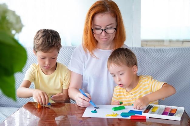 Due ragazzi caucasici e una donna dai capelli rossi con gli occhiali giocano con la plastilina colorata all'asilo oa casa