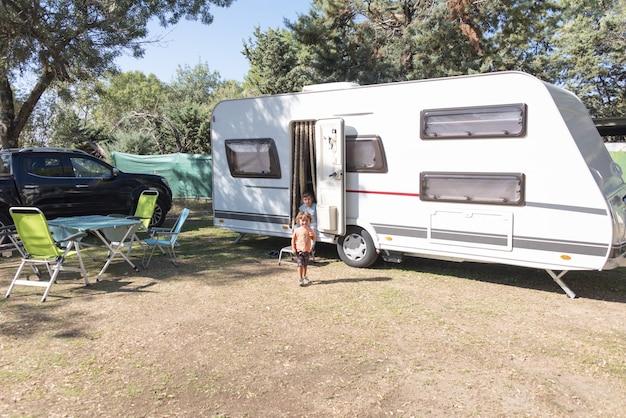 Due bambini caucasici giocano e trascorrono vacanze alternative in roulotte