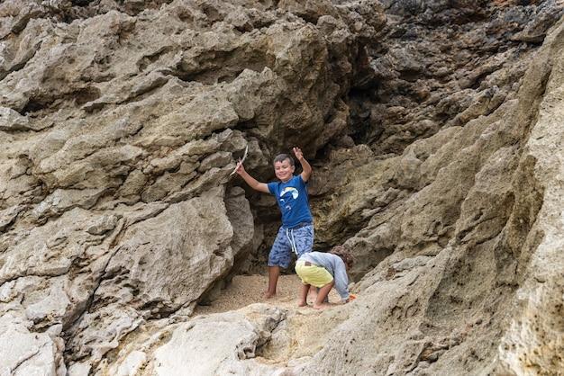 Due bambini caucasici che giocano al tramonto sulla spiaggia