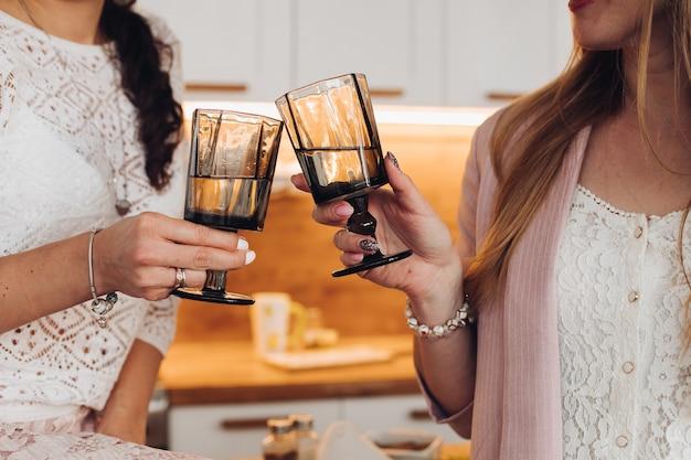 Due ragazze caucasiche bevono insieme l'acqua con i vetri in cucina
