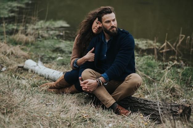Due amanti caucasici sono seduti sulla riva del lago. la giovane coppia sta abbracciando il giorno di autunno all'aperto. san valentino.