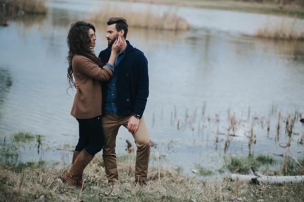 Due amanti caucasici vicino al lago. un uomo barbuto e una donna riccia innamorata. san valentino.