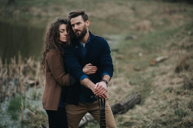 Due amanti caucasici vicino al lago. la giovane coppia sta abbracciando il giorno di autunno all'aperto. un uomo barbuto e una donna riccia innamorata. san valentino.