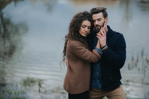 Due amanti caucasici vicino al lago. la giovane coppia sta abbracciando il giorno di autunno all'aperto. san valentino.