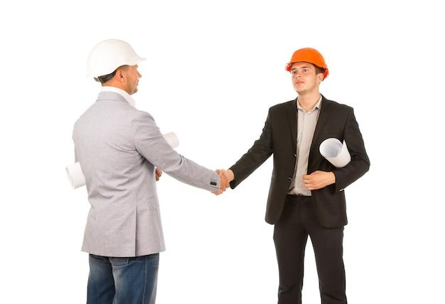 Due ingegneri caucasici di mezza età che si stringono la mano con i progetti. isolato su sfondo bianco.