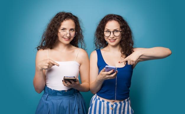 Due sorelle caucasiche che indicano il telefono mentre indossano occhiali da vista e capelli ricci su una parete blu
