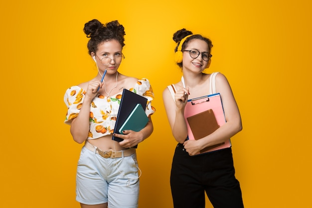 Due ragazze caucasiche dell'università in posa su una parete gialla con alcuni libri e cartelle che indossano occhiali e auricolari