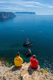 Due giovani uomini caucasici viaggiatori in giacche gialle e rosse seduti in alto sopra il mare, sullo sfondo di scogliere costiere, calmo mare azzurro, rocce orest e pilad, capo fiolent a balaklava crimea.