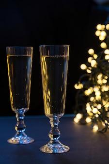 Due bicchieri di champagne a natale. luci sfocate sullo sfondo del bokeh. atmosfera romantica