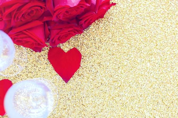 Due bicchieri di champagne, un mazzo di rose rosse e un cuore di petali giace sul lato su un brillante oro...