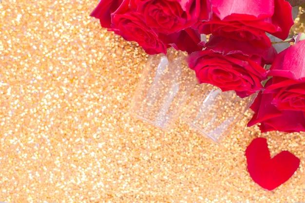 Due bicchieri di champagne e un mazzo di rose rosse si trovano nell'angolo superiore su uno sfondo dorato brillante...