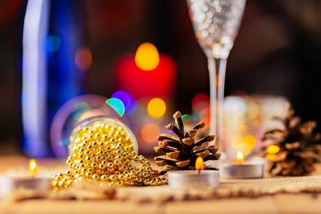 Due bicchieri di champagne con perline di natale. decorazioni natalizie in stile rustico su sfondo luminoso con luci. pigne e candele accese sullo sfondo bokeh