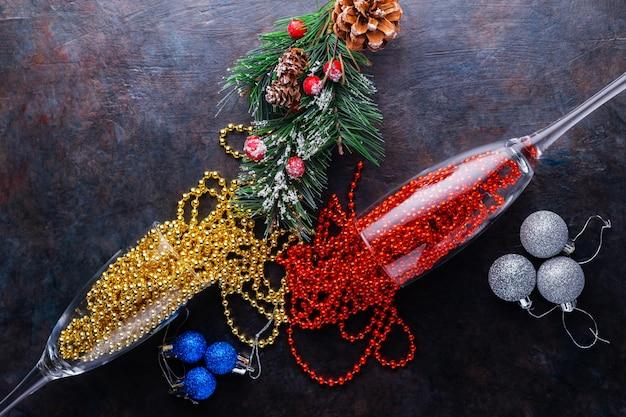 Due bicchieri di champagne con perline di natale su sfondo scuro. palle di natale, perline multicolori e ramo di abete. concetto di festa. vista dall'alto