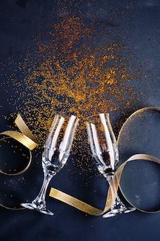 Due bicchieri di champagne con glitter su sfondo nero che simboleggiano una celebrazione