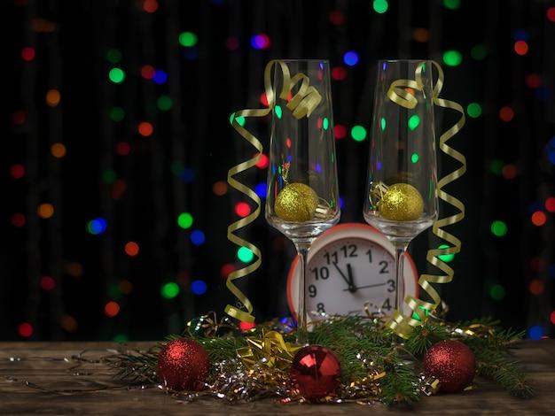 Due bicchieri di champagne con ornamenti e un orologio su un bokeh