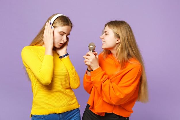 Due affascinanti sorelle gemelle bionde in abiti vivaci ascoltano musica con le cuffie, cantano una canzone nel microfono isolato sulla parete blu viola. concetto di stile di vita familiare di persone.