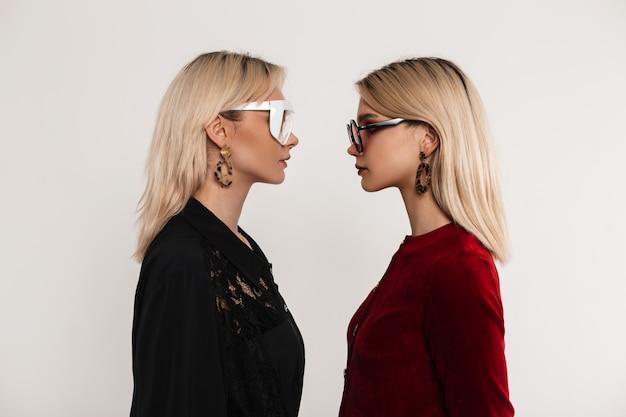 Due affascinanti sorelle bionde alla moda in eleganti bei vestiti in eleganti occhiali colorati si guardano l'un l'altro vicino a un muro vintage al chiuso