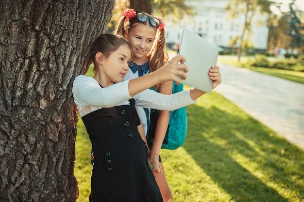 Due affascinanti ragazze in età scolare sono in piedi vicino all'albero accanto alla scuola e giocano sul tablet. le scolarette fanno un selfie