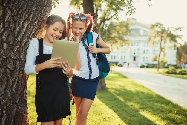 Due affascinanti ragazze in età scolare stanno accanto all'albero vicino alla scuola e giocano sul tablet.