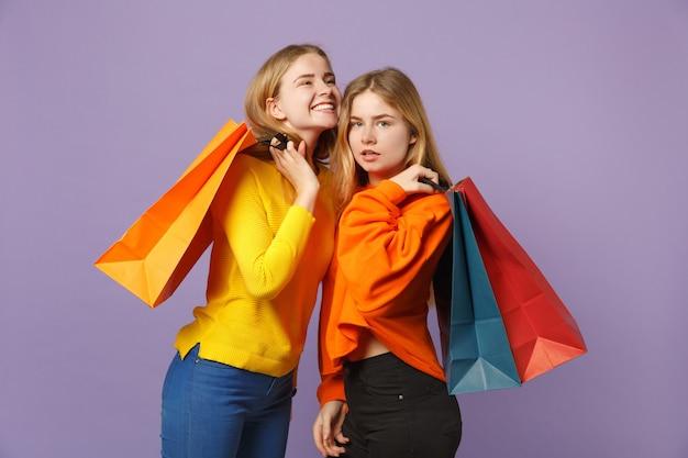 Due affascinanti giovani sorelle gemelle bionde in abiti vivaci tengono il pacchetto con gli acquisti dopo lo shopping isolato sulla parete blu viola. concetto di stile di vita familiare di persone.