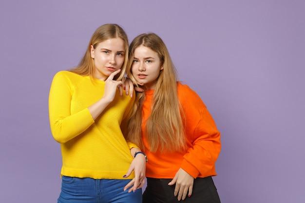 Due affascinanti giovani sorelle gemelle bionde ragazze in abiti colorati vividi in piedi, isolate sulla parete blu viola pastello. concetto di stile di vita familiare di persone.