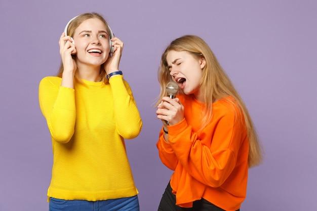 Due sorelle gemelle bionde allegre in abiti vivaci ascoltano musica con le cuffie, cantano una canzone nel microfono isolato sulla parete blu viola. concetto di stile di vita familiare di persone.