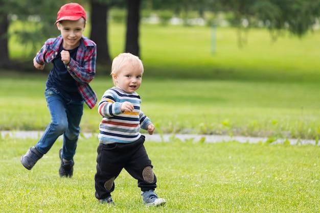 Due allegri fratelli di età diverse si divertono, corrono attraverso il campo verde in una calda giornata estiva.