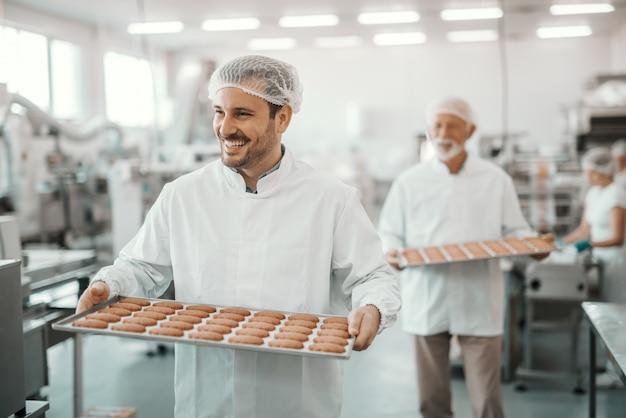 Due dipendenti caucasici allegri che trasportano vassoi con biscotti freschi. entrambi sono vestiti con uniformi bianche sterili e con retine per capelli. interno della pianta alimentare.