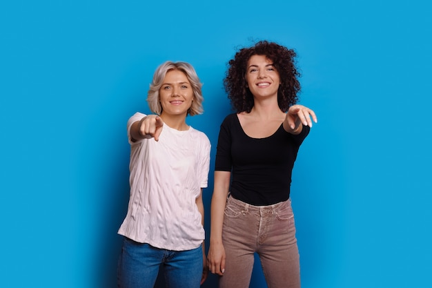 Due donne caucasiche allegre vestite in jeans con i capelli ricci stanno puntando alla telecamera mentre sorridono su uno sfondo blu