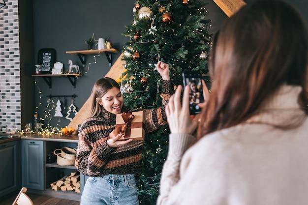 Due amici allegri delle donne caucasiche divertendosi e facendo foto con regali e albero di natale.
