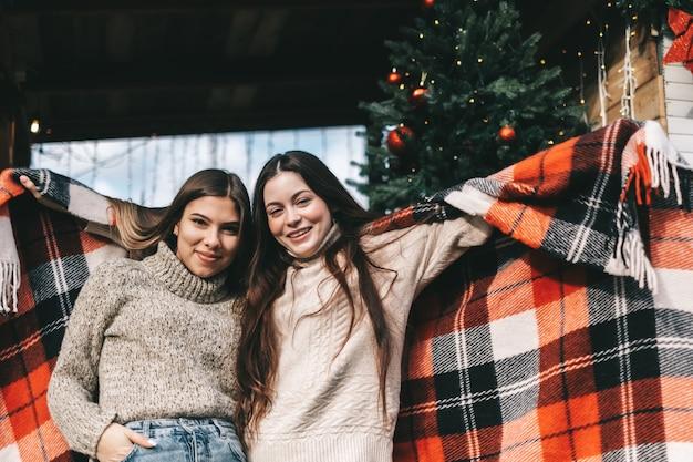 Due amici allegri donne caucasiche in posa sul cortile con decorazioni natalizie