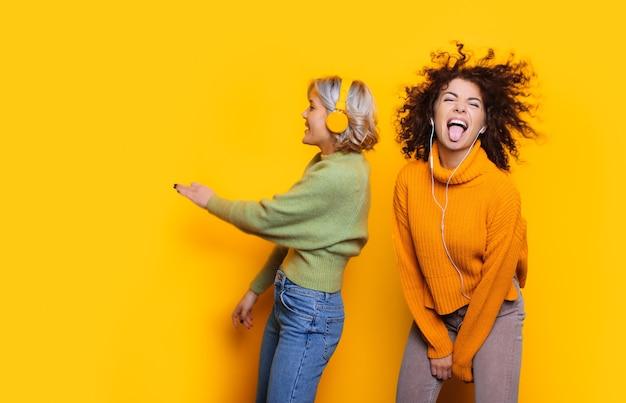 Due donne caucasiche allegre con capelli ricci ballare e ascoltare musica con le cuffie in posa sullo spazio giallo della copia