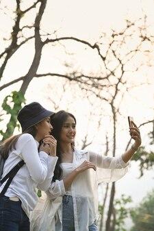 Due allegri studenti di college che utilizzano smart phone prendendo selfie al parco.