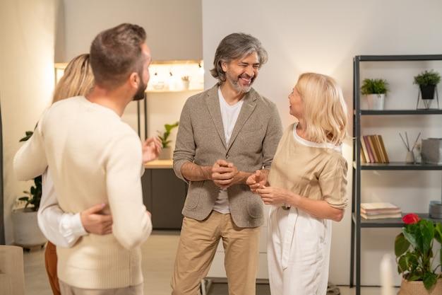Due coppie allegre in abbigliamento casual in piedi l'una di fronte all'altra nel soggiorno o nel corridoio e discutono tra loro delle ultime notizie