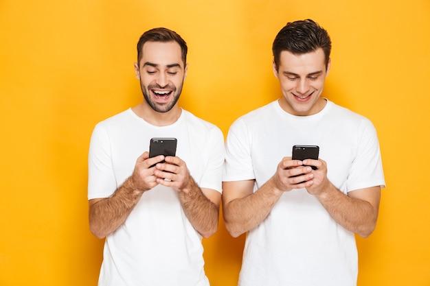 Due amici uomini eccitati allegri che indossano magliette bianche in piedi isolate su un muro giallo, usando i telefoni cellulari