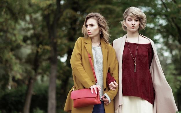 Due ragazze alla moda allegre nel parco autunnale