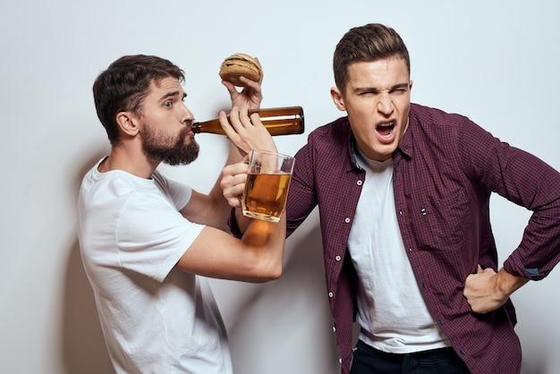 Due amici allegri che bevono birra ubriaco divertimento lifestyle comunicazione sfondo chiaro.
